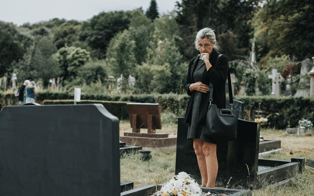 familiare che visita un defunto in cimitero